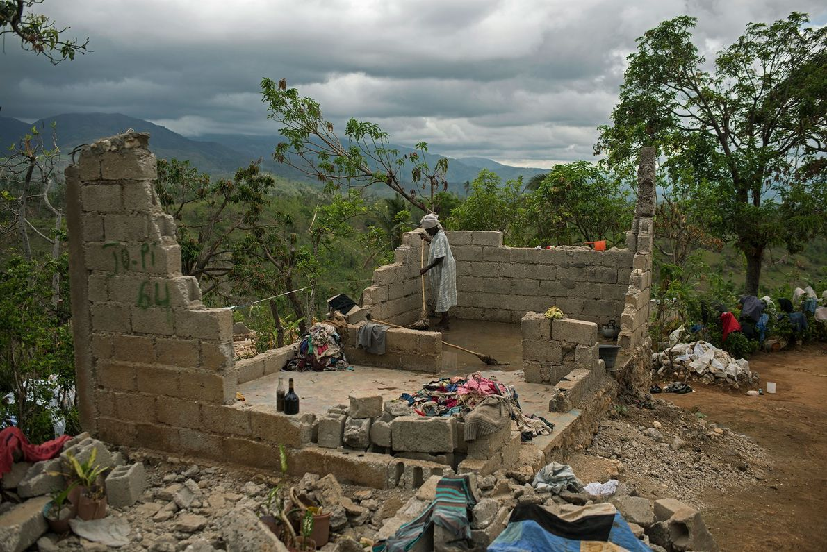 A woman attempts to clean what is left of her home in the mountains of southern ...
