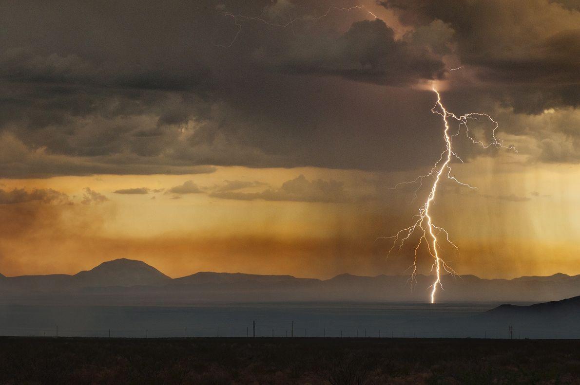 Silent but steady, single bolt of lightning bursts through a golden sky.
