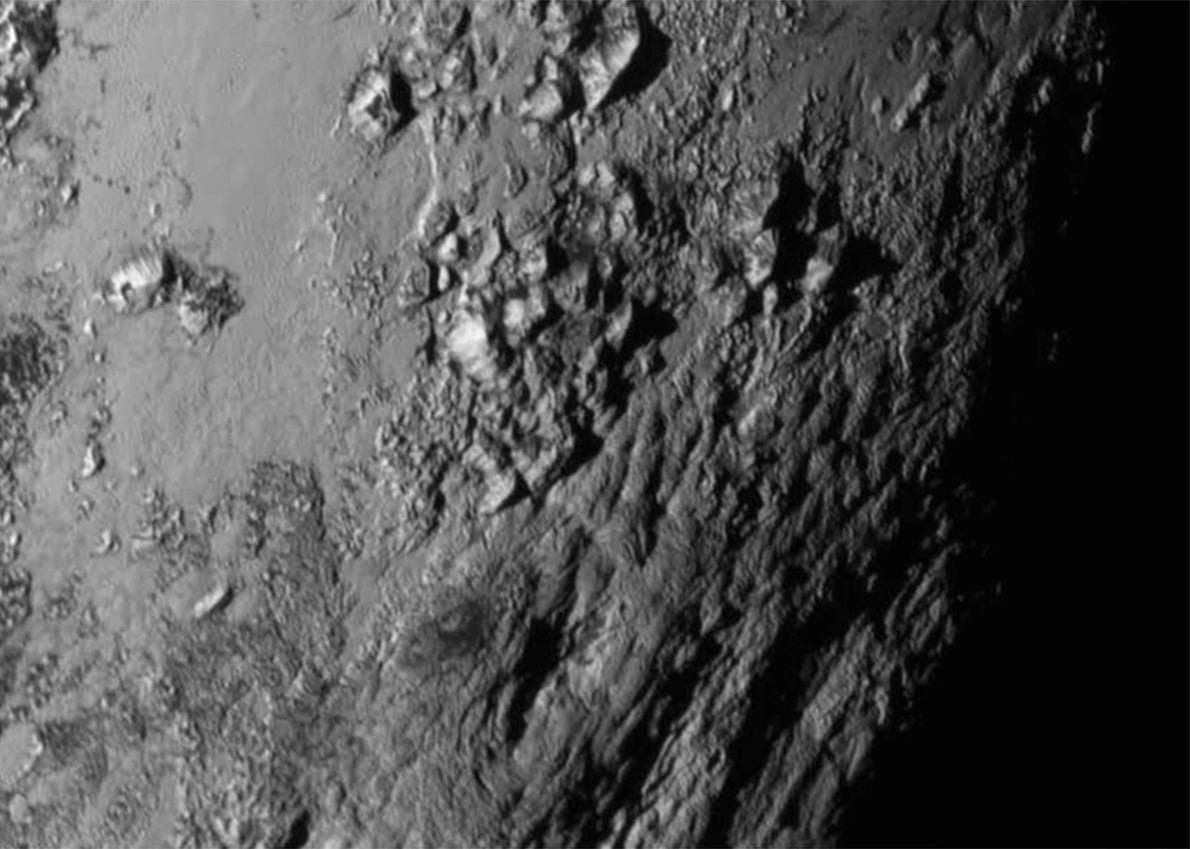 The first close-up view of Pluto's surface reveals that mountains of ice rise 3,500 metres (11,000 ...