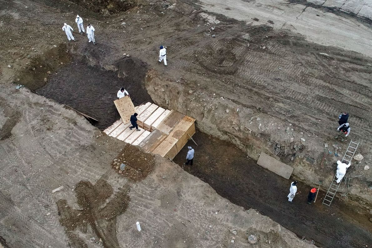 Workers wearing personal protective equipment bury bodies on April 9, 2020, the day the New York ...