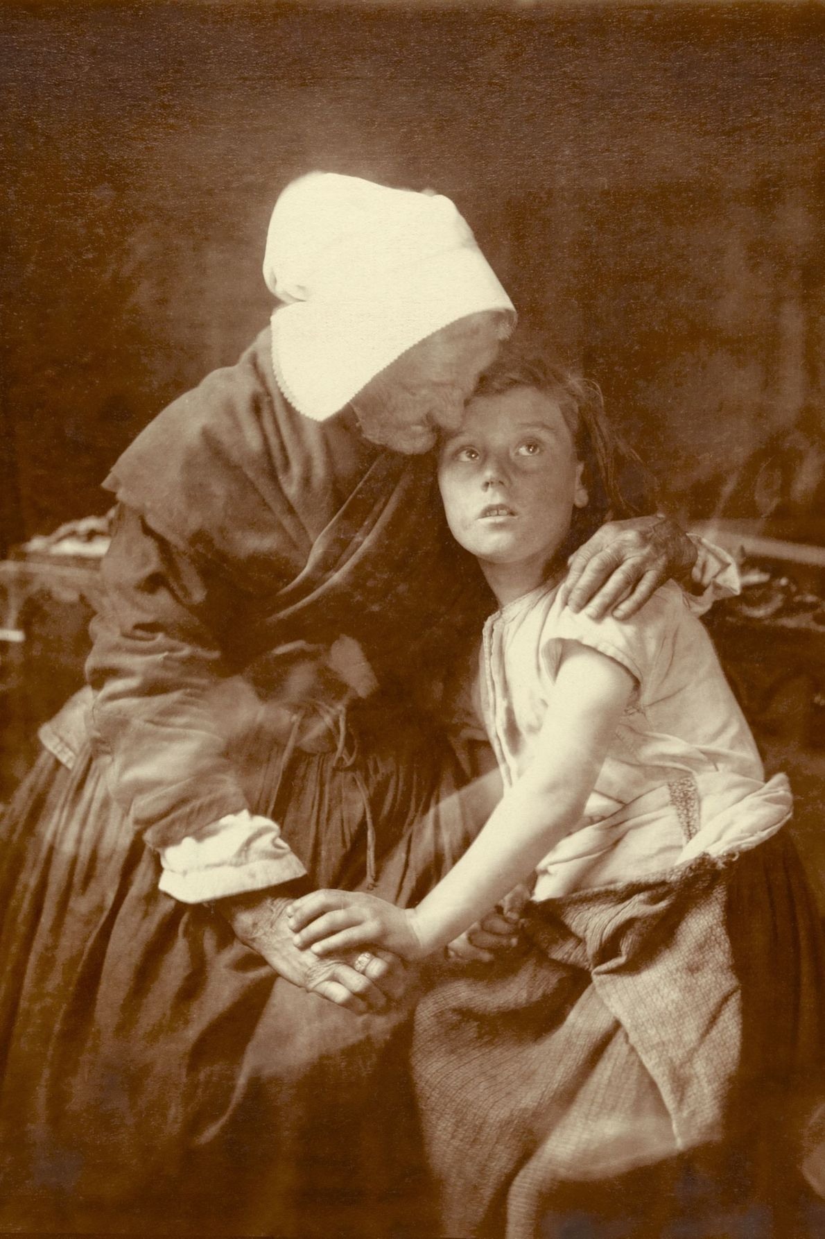 An elderly Flemish grandmother in Belgium hugs a child.