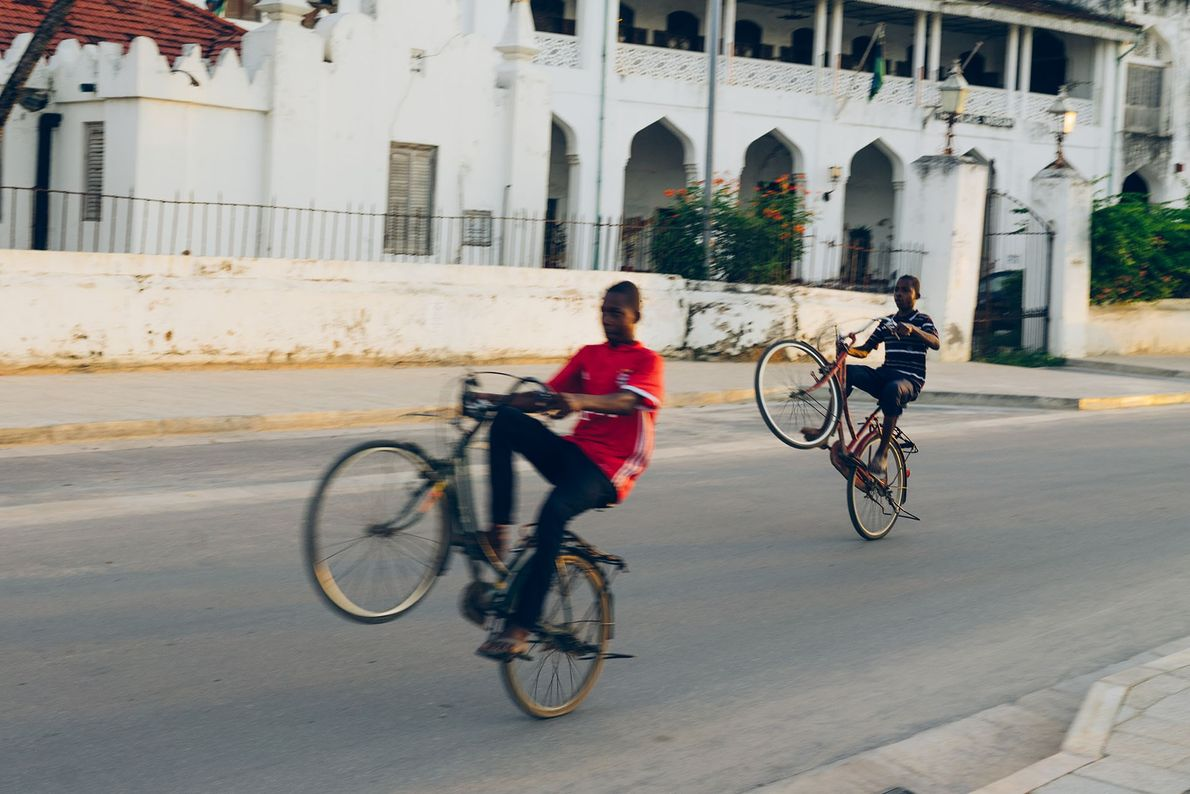 Young boys showing off their wheelie skills along the harbour front of Stone Town