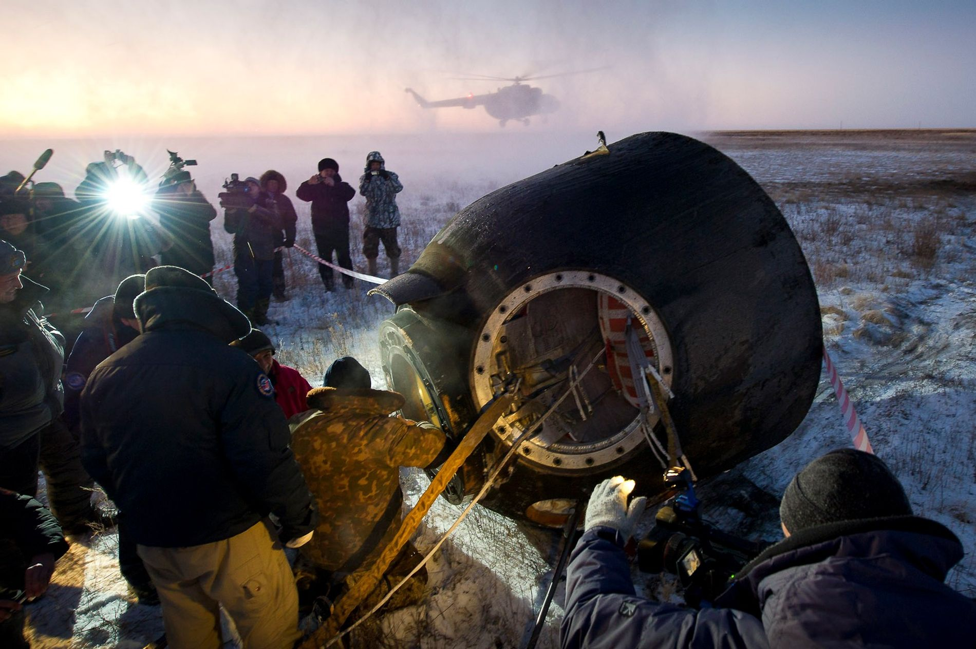 Support personnel help the Soyuz TMA-02M passengers—NASA astronaut Mike Fossum, Russian cosmonaut Sergei Volkov, and Japanese astronaut Satoshi Furuka—disembark following their five-month mission on the International Space Station.