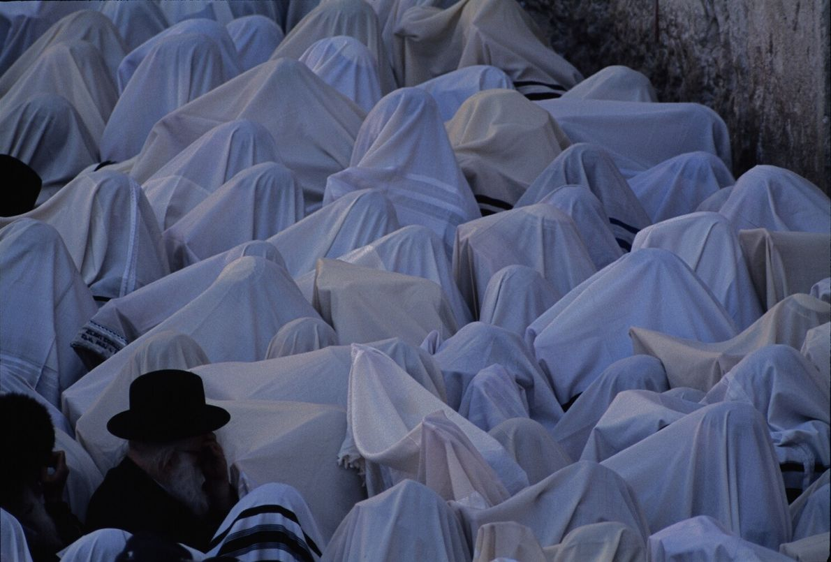 Picture of people covered in prayer shawls kneeling before the Western Wall