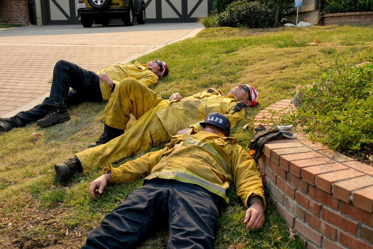 Exhausted firefighters rest on Glenbridge Road in Westlake Village after fighting the Woolsey Fire.