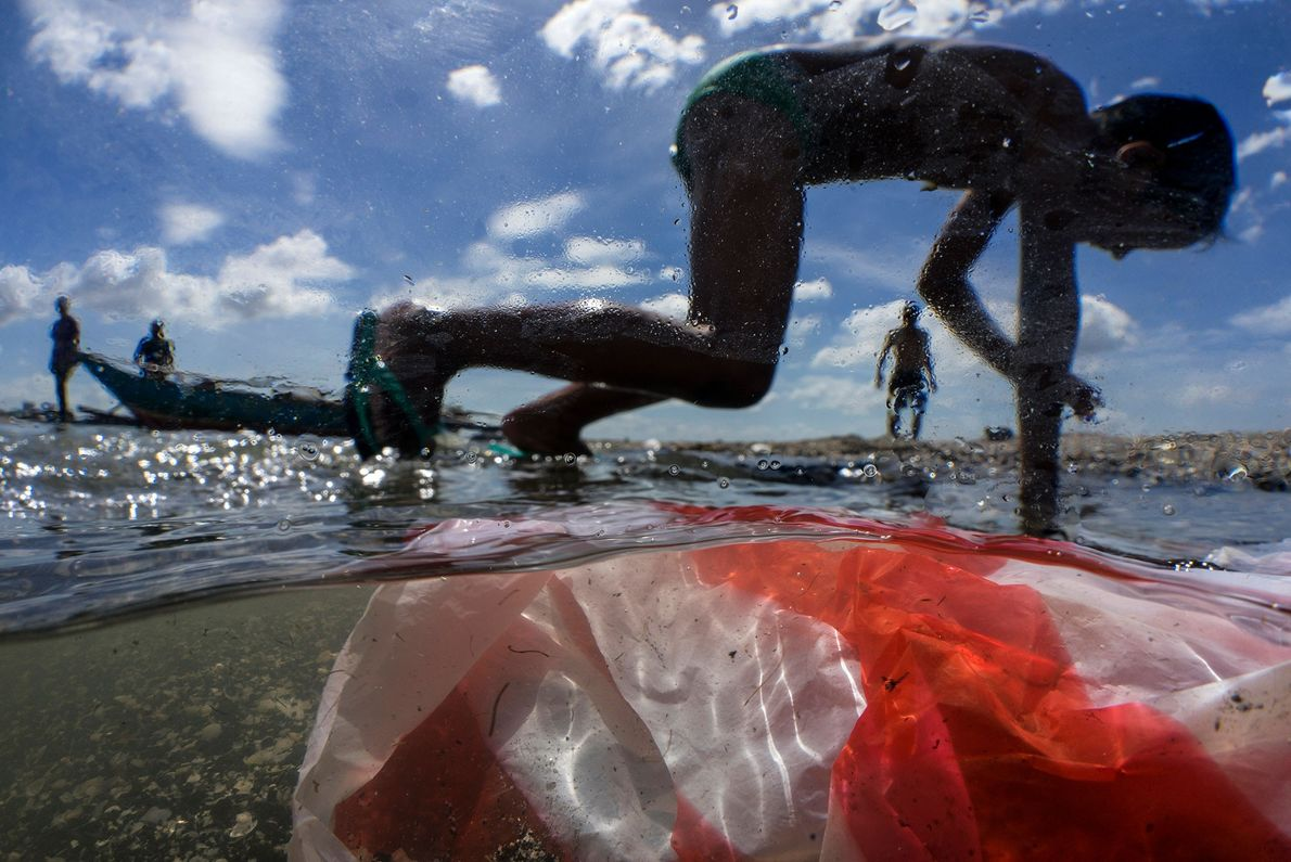 Children play on the shore of Manila Bay in the Philippines, which is polluted by household ...