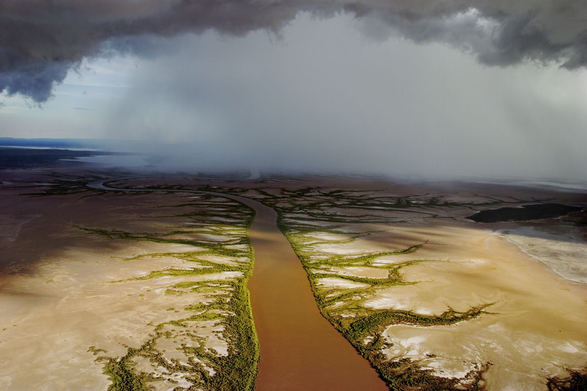 Low-hanging rain clouds form a over a river in Western Australia.