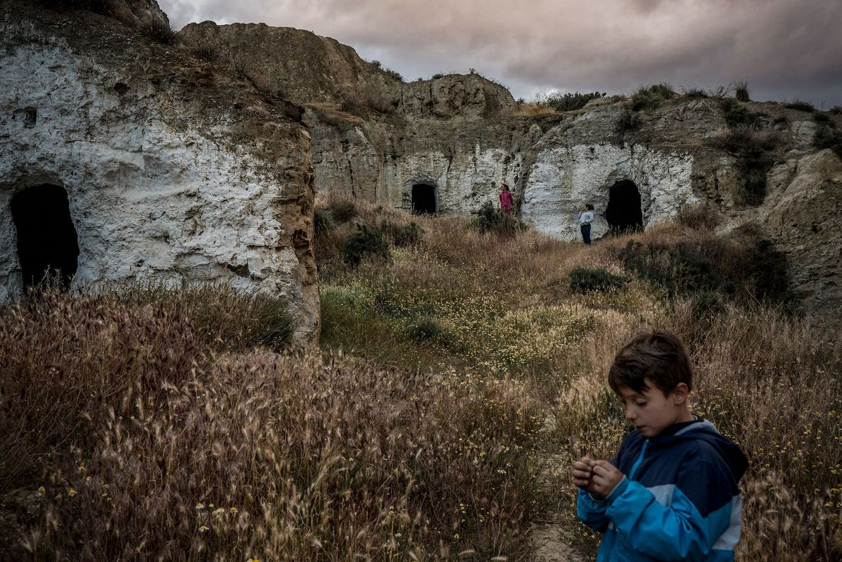 Children play in abandoned caves next to their own cave home. In the past, every cave ...