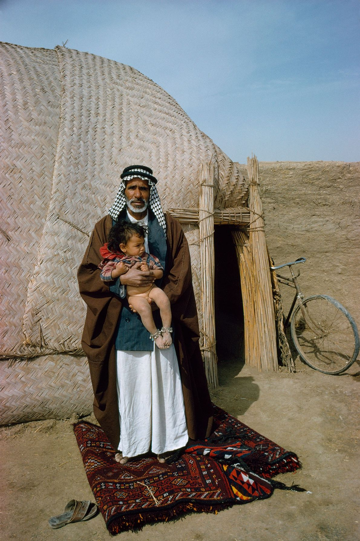 A man holds his son while standing on the rug outside his rush-mat hut in Iraq.