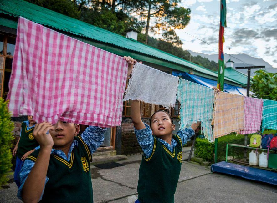 Exiled Tibetan children hang laundry before going to school in the Tibetan Children's Village in Dharmsala, ...