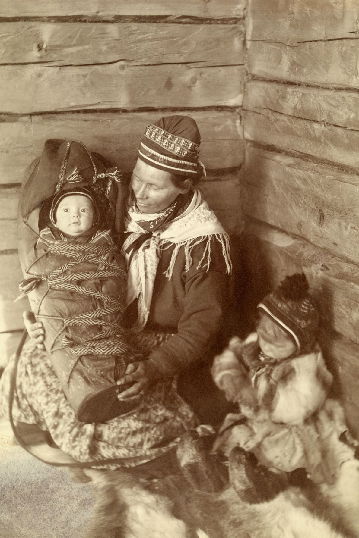 A Sami woman, toddler, and infant in Lapland, Finland, sit on pelts that soften their surroundings ...