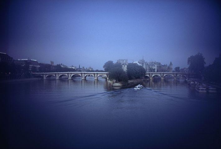 Spring night descends softly on the Seine, whose arms clasp the Île de la Cité's downriver ...