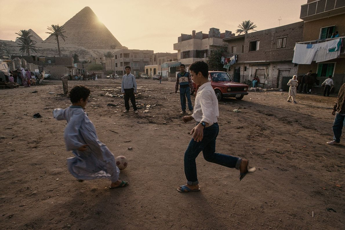 Village children play football at the foot of Pyramids of Giza in Egypt.