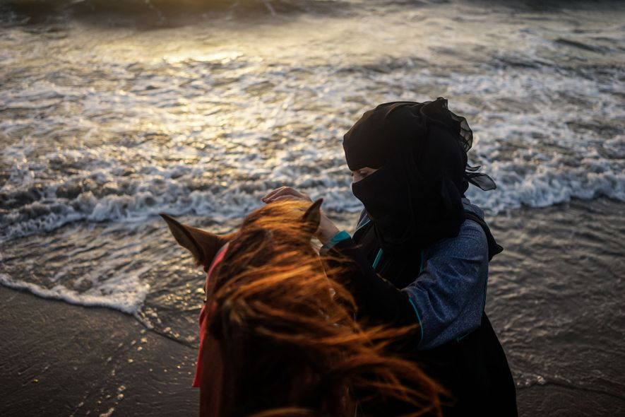 A woman calms a horse against the backdrop of the Red Sea in Hodeidah.