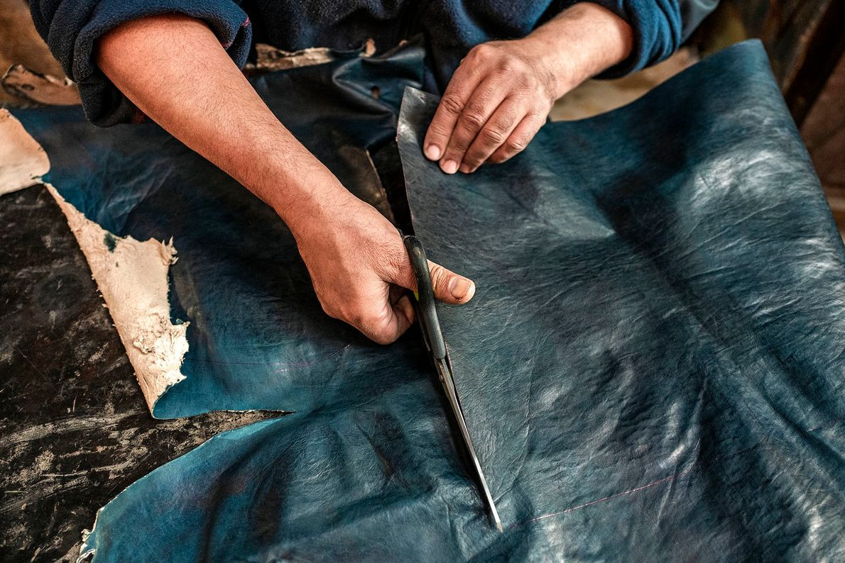 An artisan carefully cuts a dyed hide into the several parts that will make up the ...