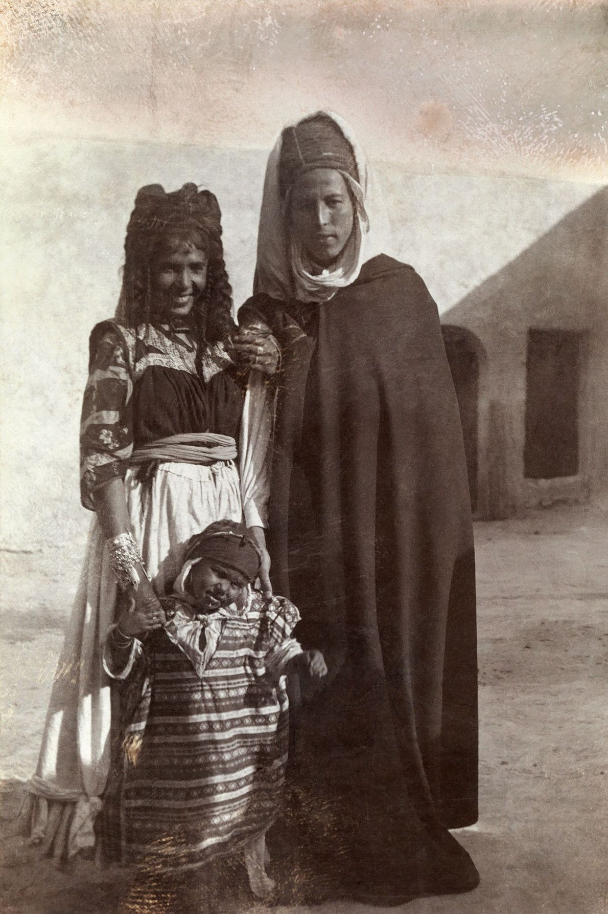A young Algerian couple and their toddler pose in front of a building in Biskra, Algeria, ...