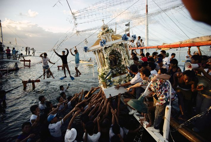 Faithful residents reach for a palanquin containing a religious image in the Philippines.