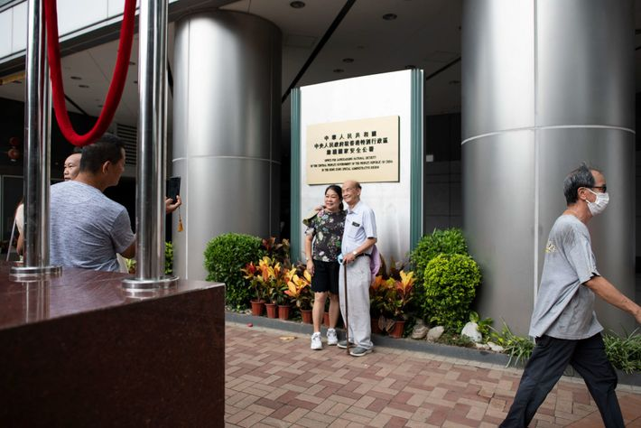 People pose for photos outside the new Office for Safeguarding National Security on July 8, the ...