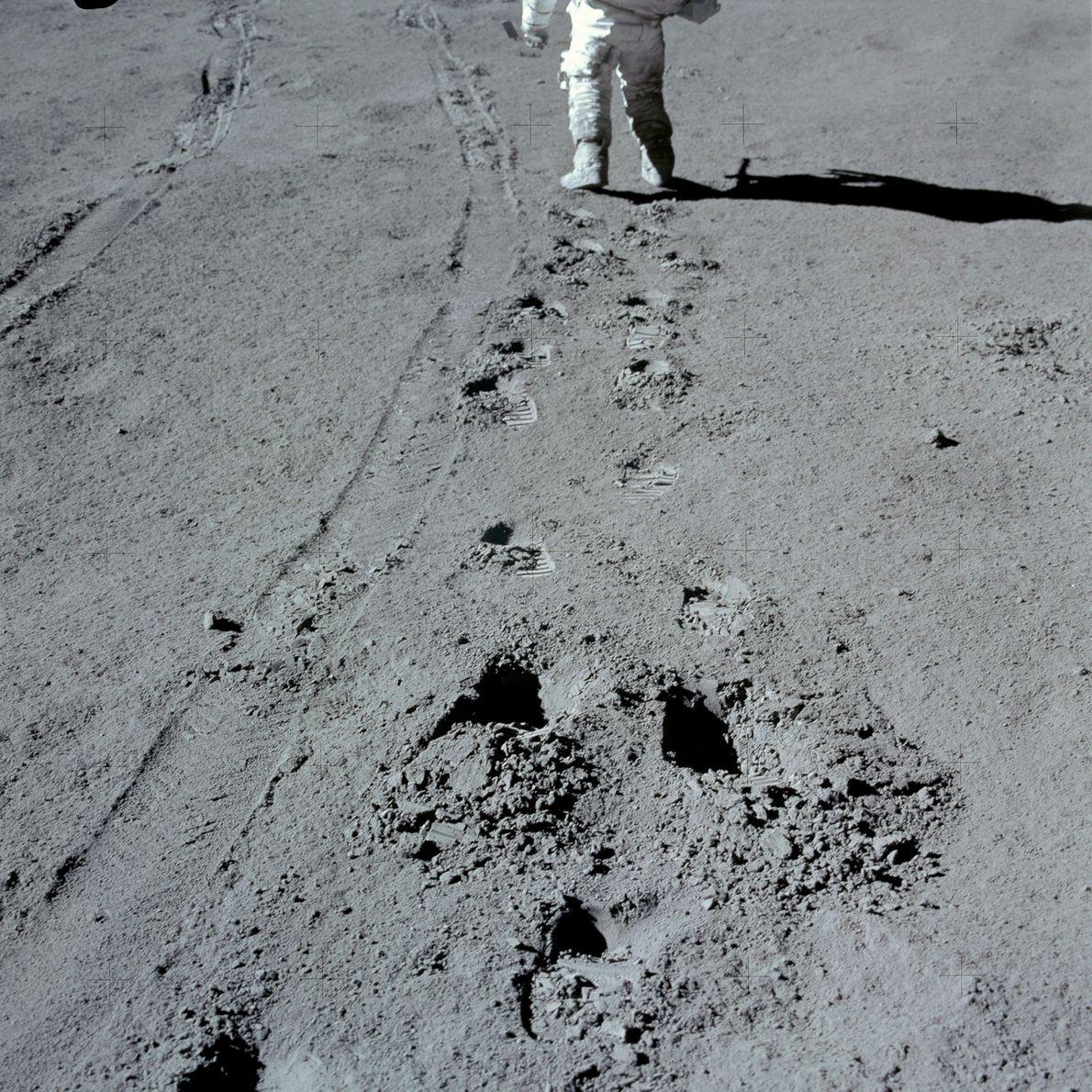 An Apollo 15 astronaut walks next to tracks left by the Lunar Roving Vehicle. Apollo 15 ...
