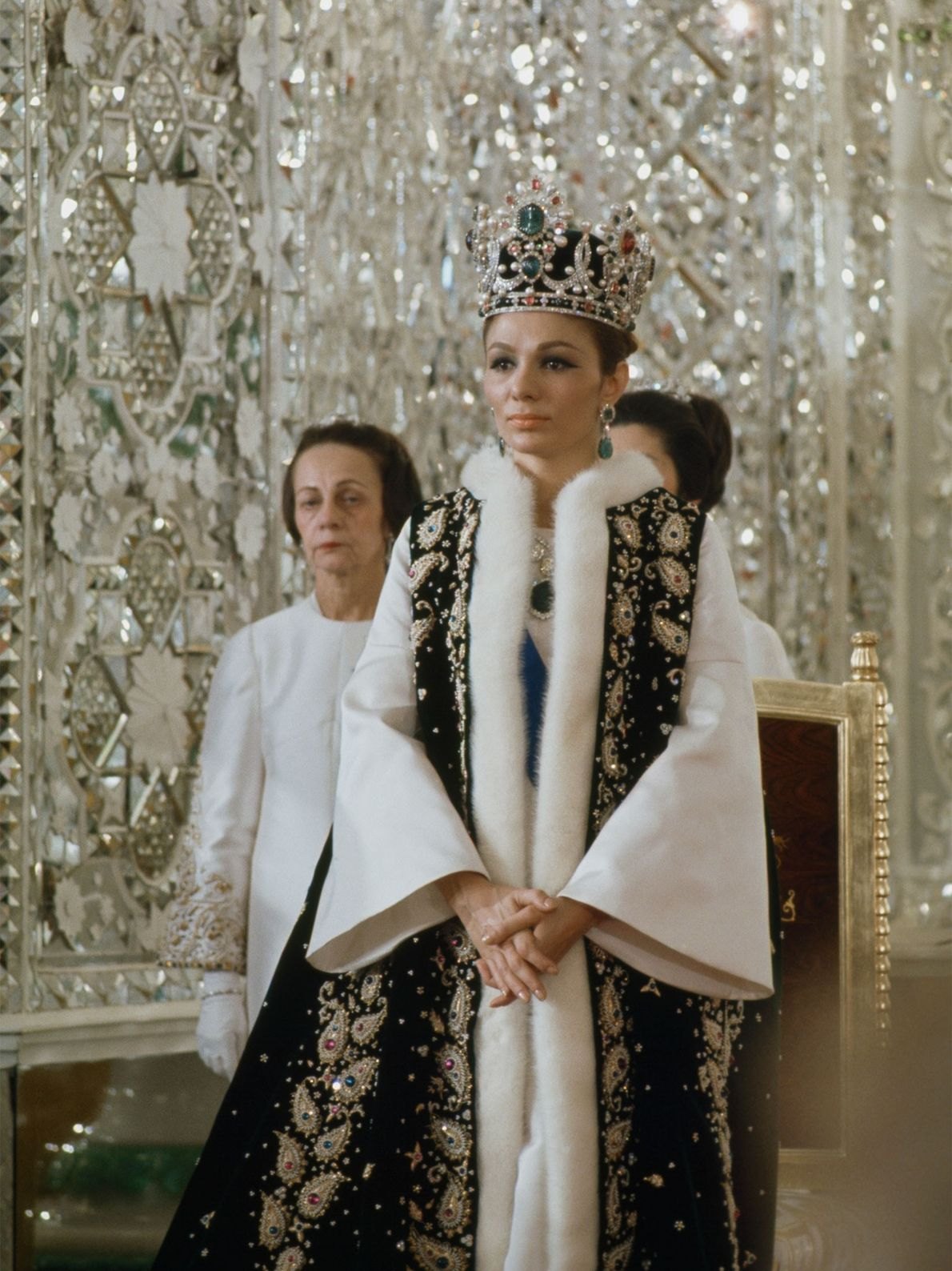 Iranian Empress Farah Pahlavi walks through Gulistan Palace dressed in ceremonial attire. The widow of Shah ...