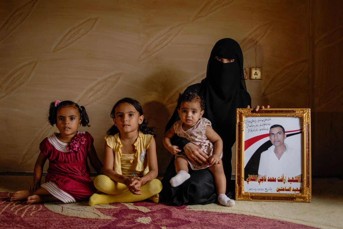A widow and her daughters pose with the portrait of the husband and father who died ...