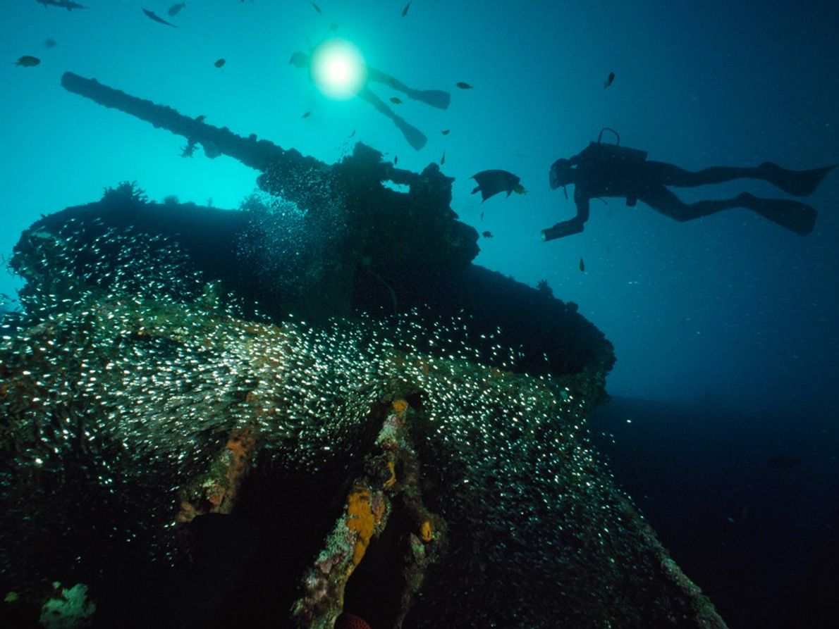 Divers swim near a guntub on the sunken U.S.S. President Coolidge near Vanuatu's Espiritu Santo Island. ...
