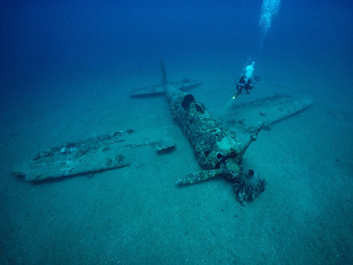 A diver explores the wreckage of a Japanese World War II fighter plane near the town ...