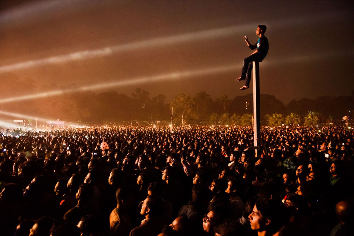 """""""A man climbs up on a pole to get a better view and takes pictures on ..."""