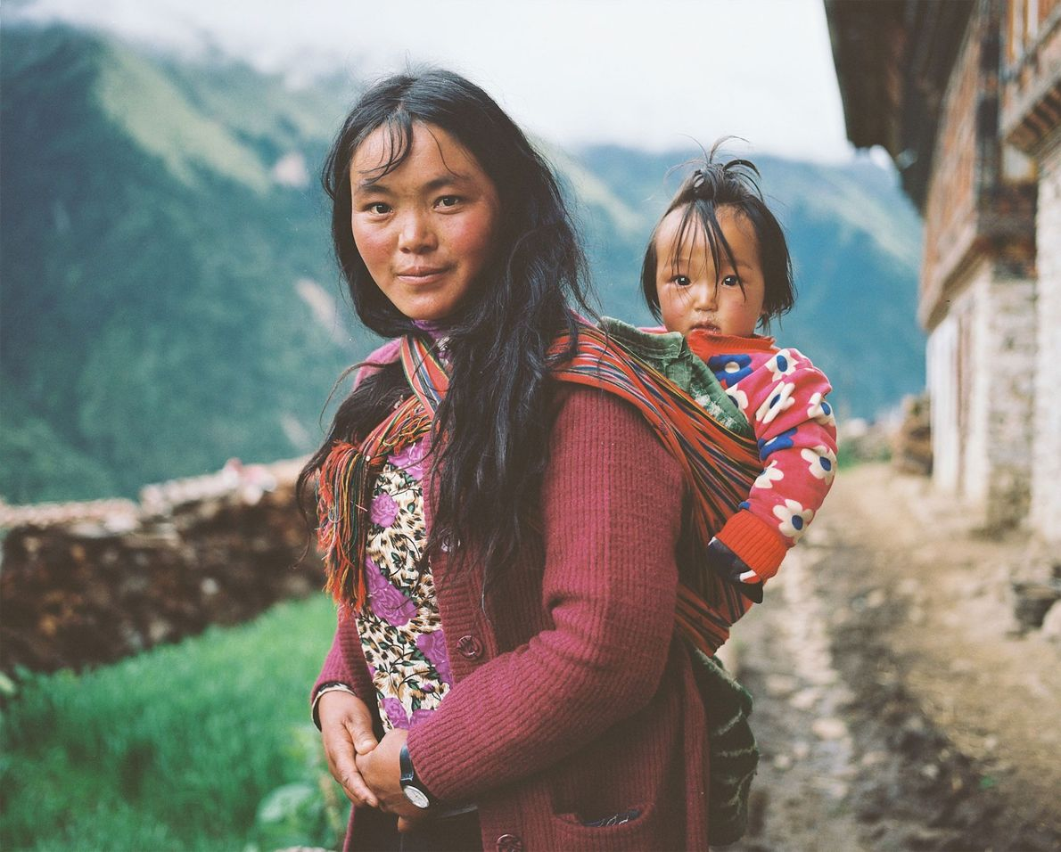 A woman from Laya carries her child on her back.