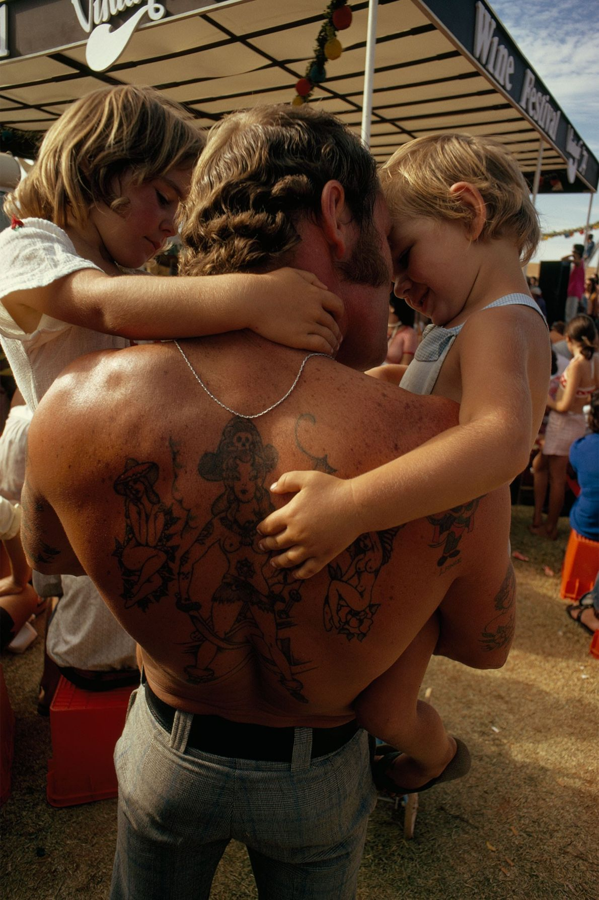 A tattooed man holds his children in his arms in Caversham, Australia.