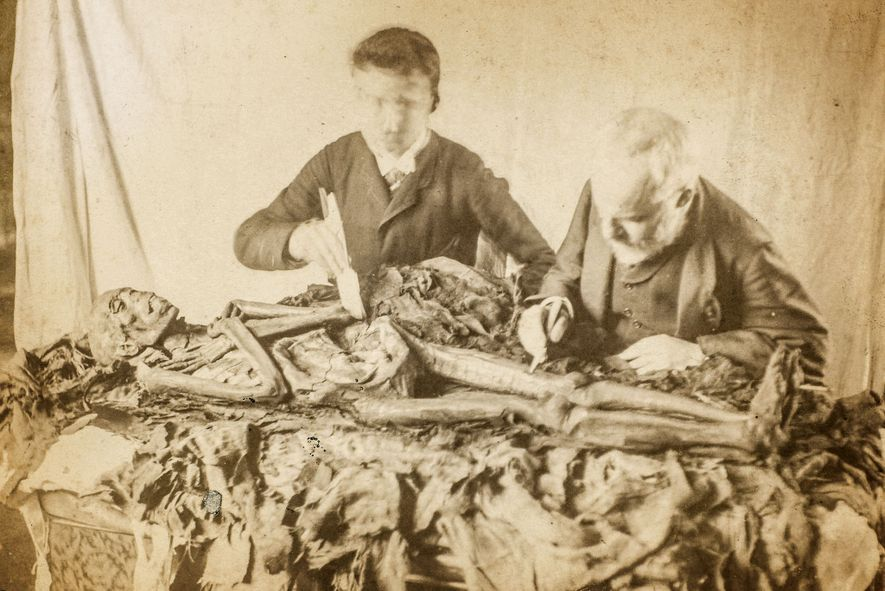 Photographed in the 19th century, two unidentified men carefully dissect a mummy, illustrating how academic attitudes ...