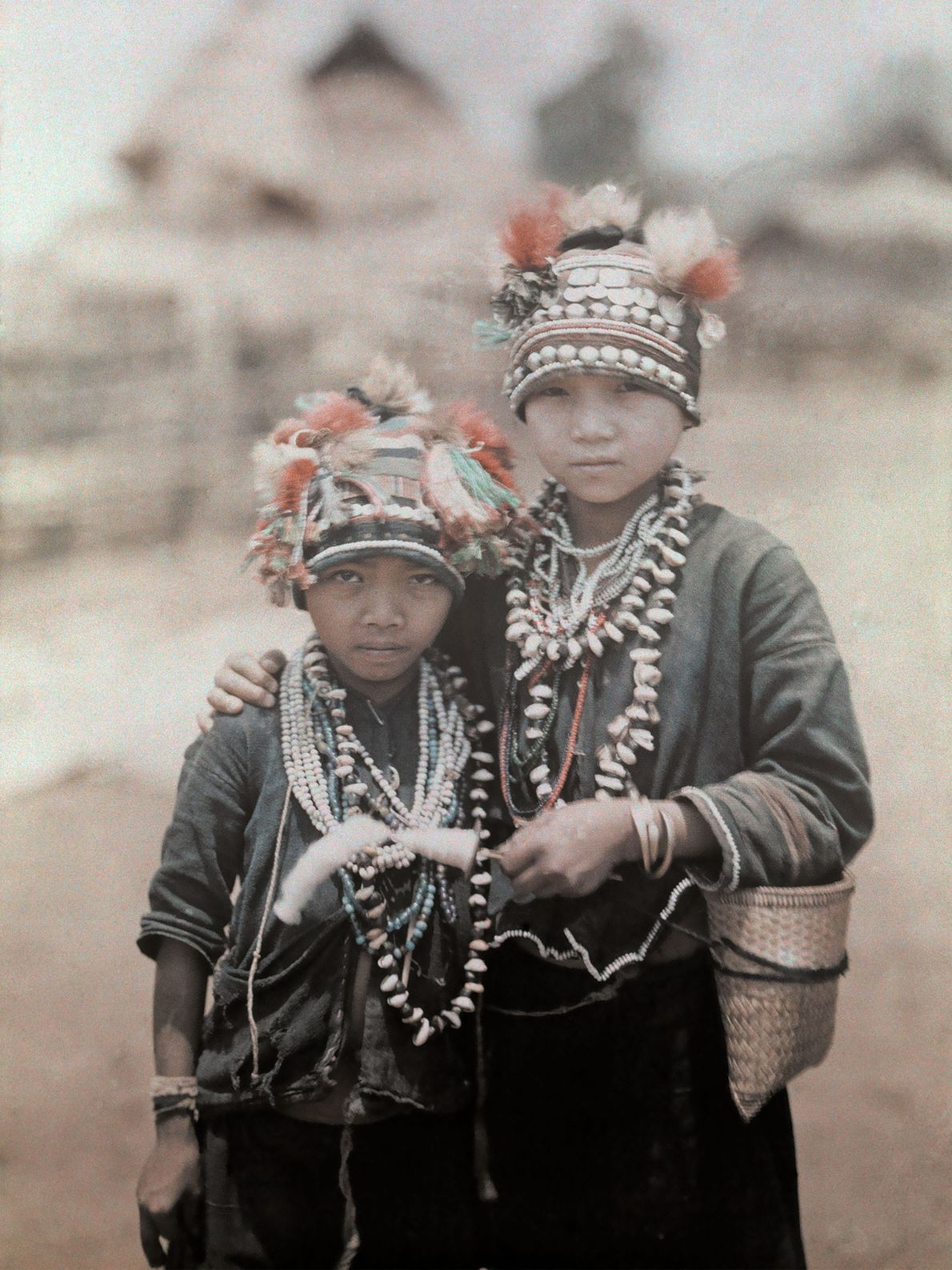 Two young boys of the Shan tribe in Myanmar wear hats covered with tassels and tufts ...