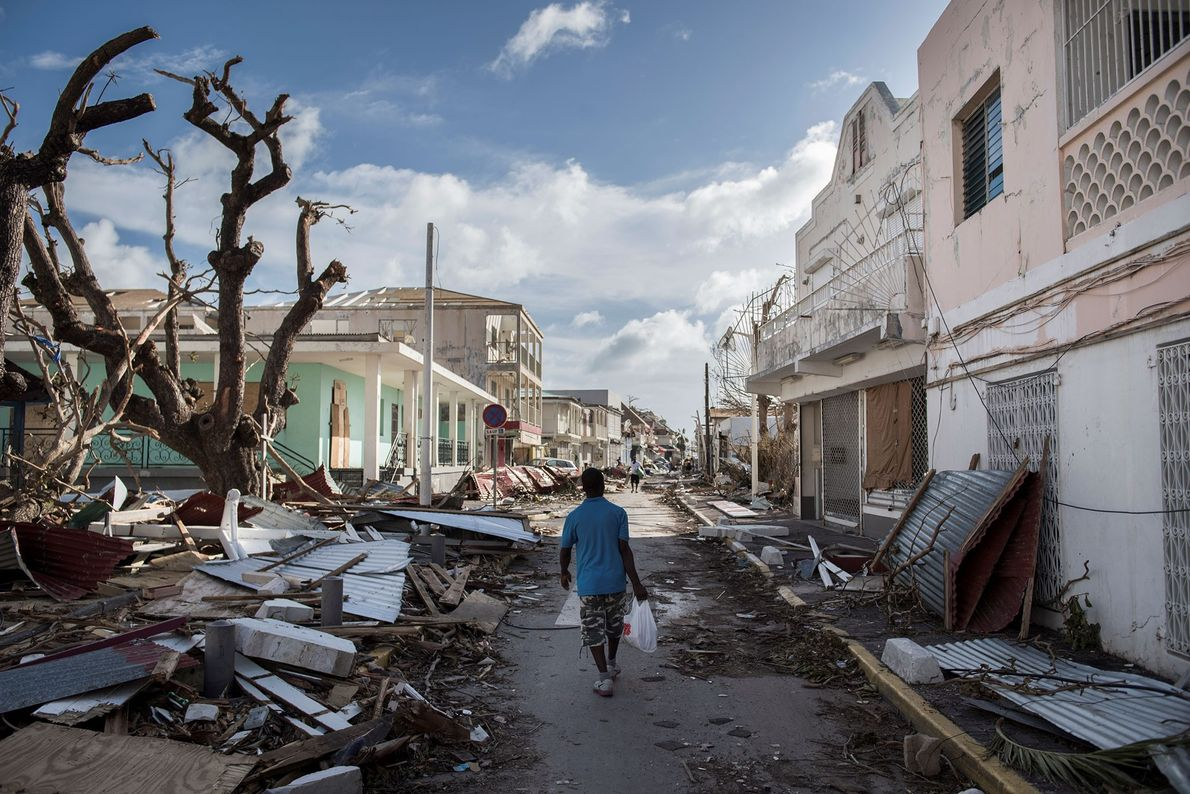 A man in St. Martin walks on a street covered in debris after Hurricane Irma hit ...