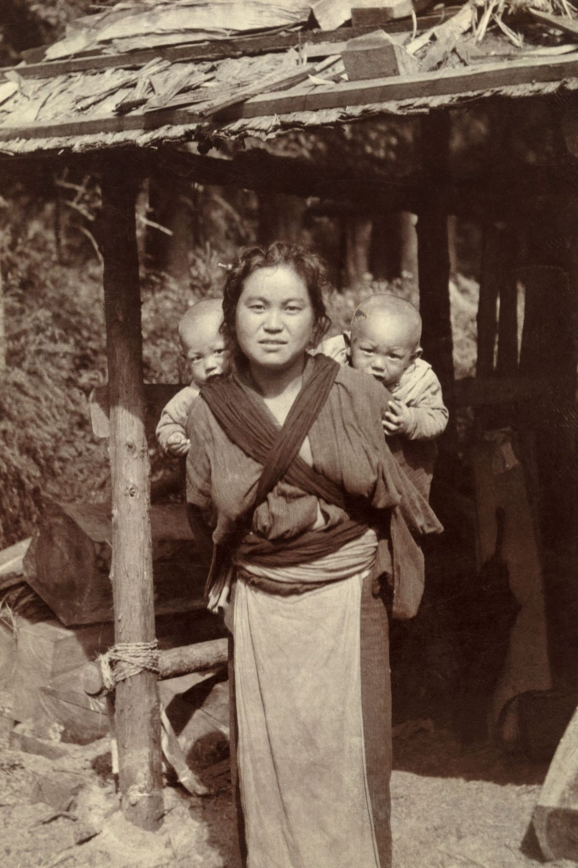 A Japanese woman carries her twins on her back with a cross wrap.