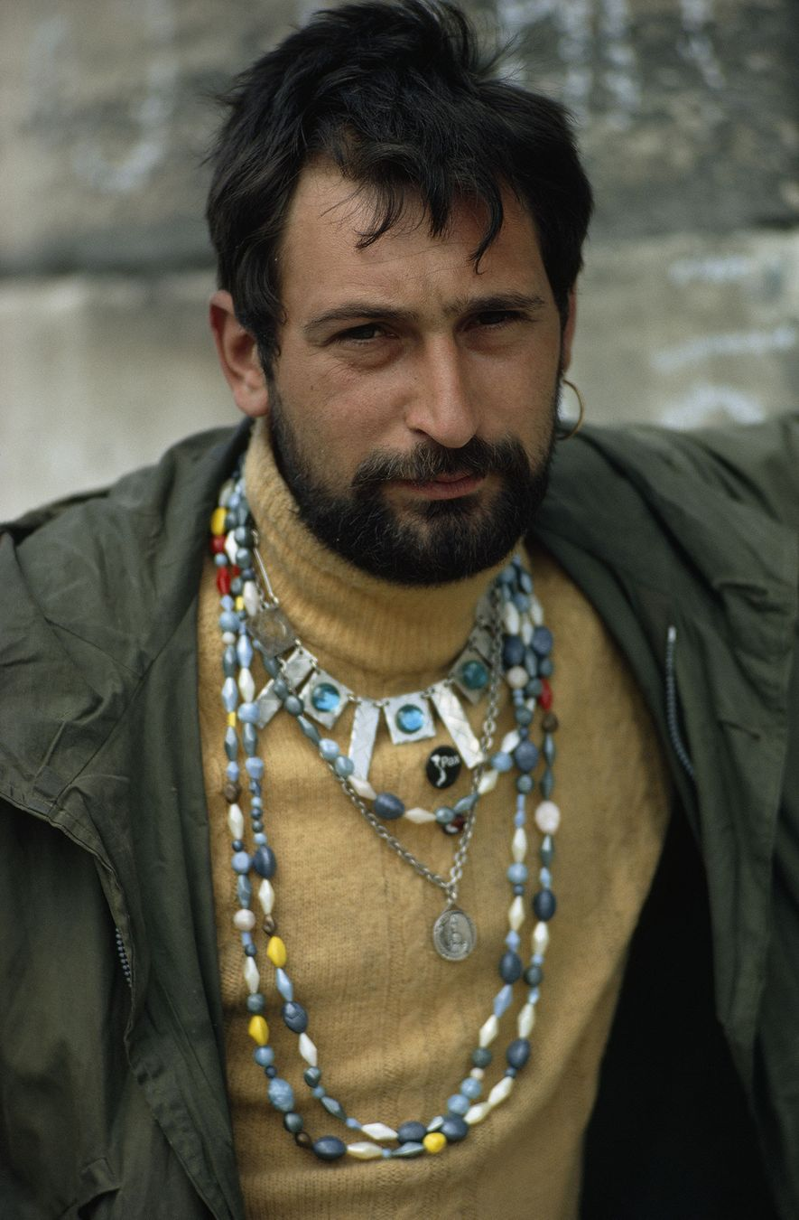 Beads, beard, and an earring adorn a young Frenchman.