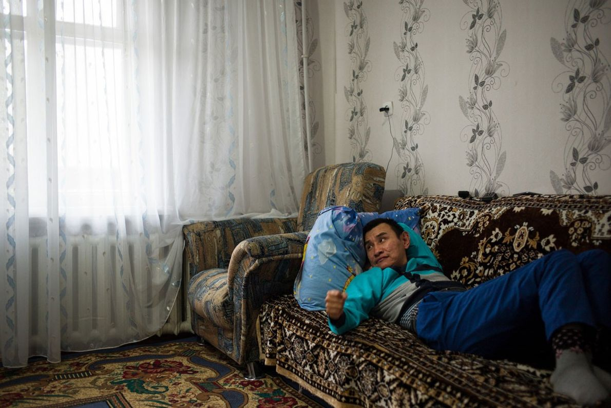 Kairat Yesimhanov, 35, sits at home in Sulbinsk, in eastern Kazakhstan. Kairat and his younger sister, ...