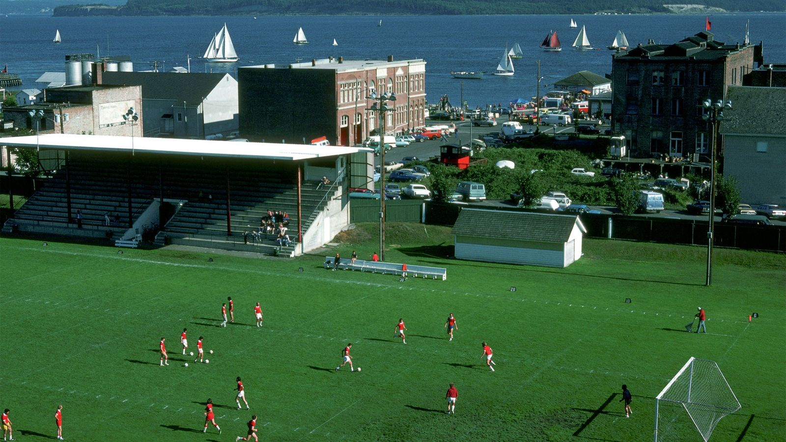 Players participate in a football game as sailboats pass through the nearby water during the Wooden ...