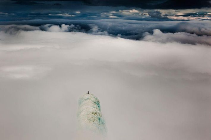Atop on of two summit pinnacles of Snaefellsjokull mountain in Iceland, climber Remi McMurtry stands above ...