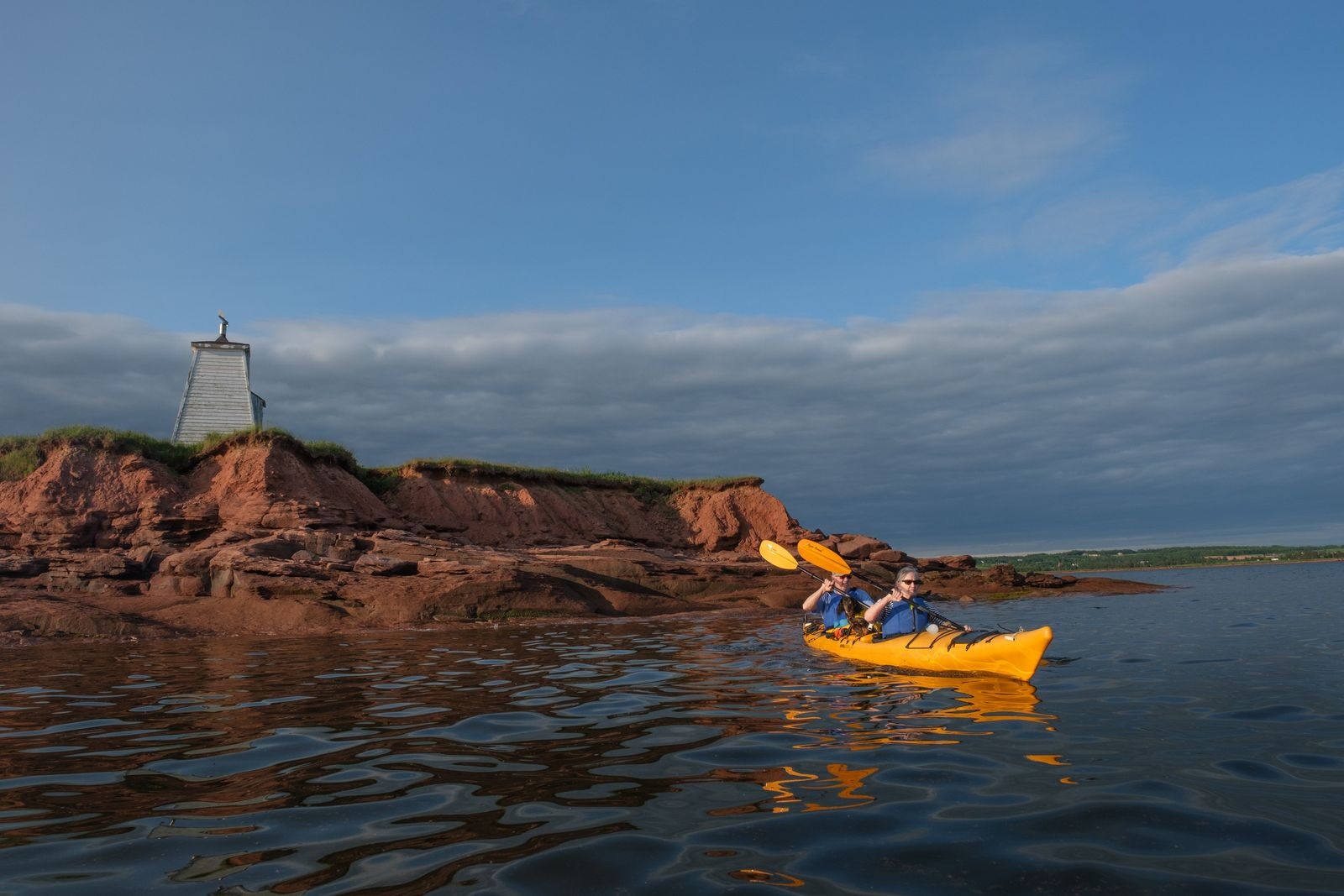 Kayakers round the point of Victoria Harbour at the entrance to Northumberland Strait, marked here by ...