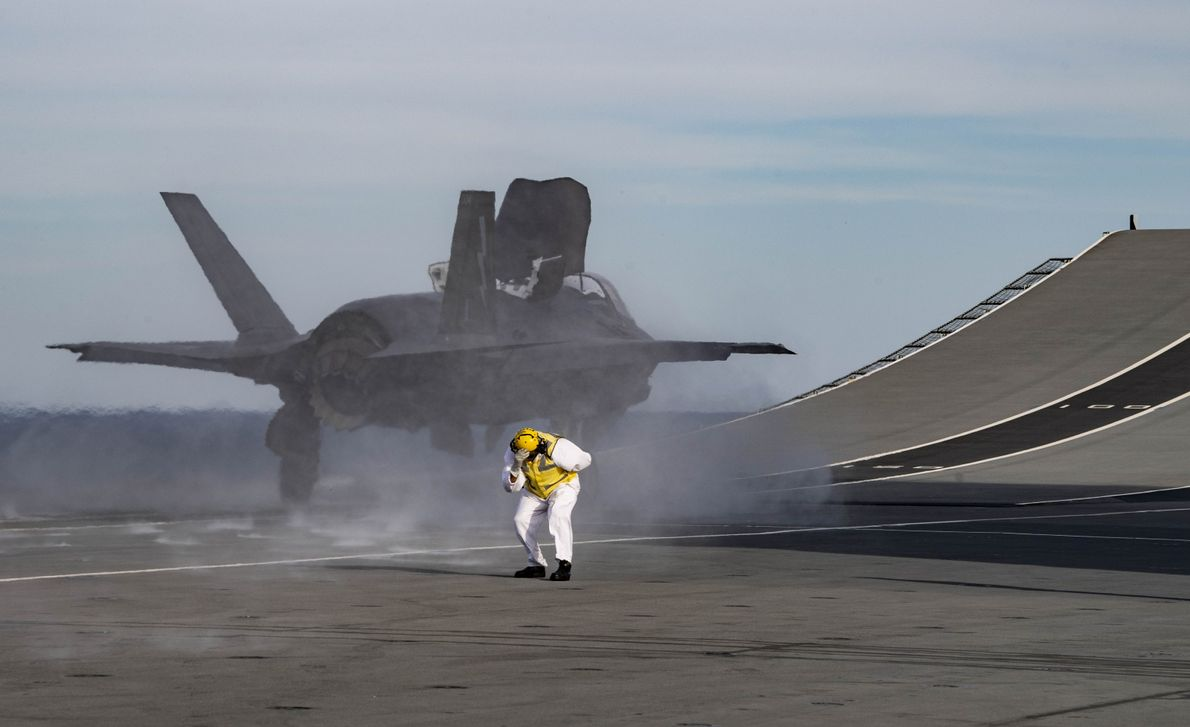 A deck crew member ducks for cover as a F-35B Lightning launches off the 'ski jump' ...