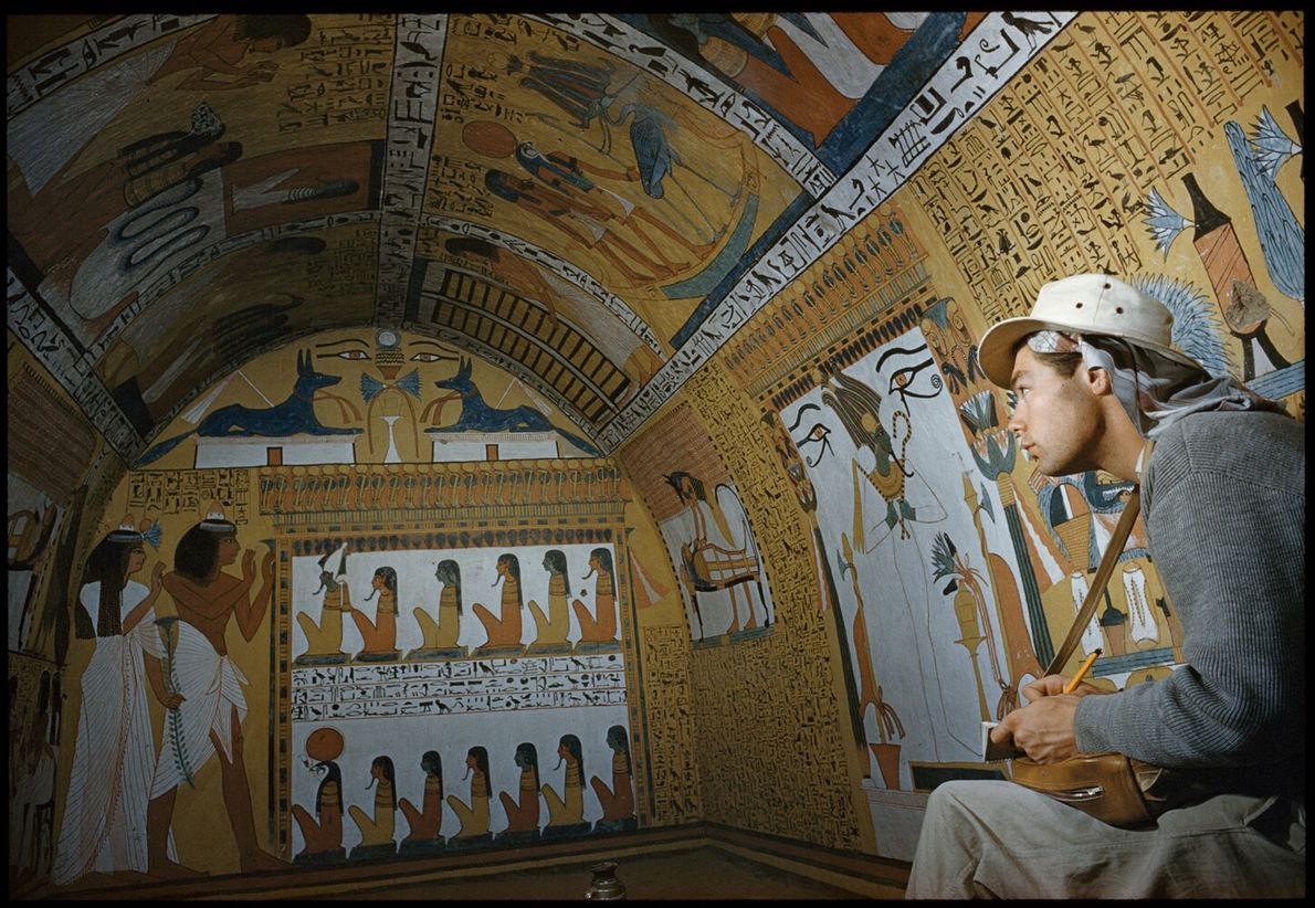 Picture of a person taking notes inside of an elaborately painted tomb in Egypt