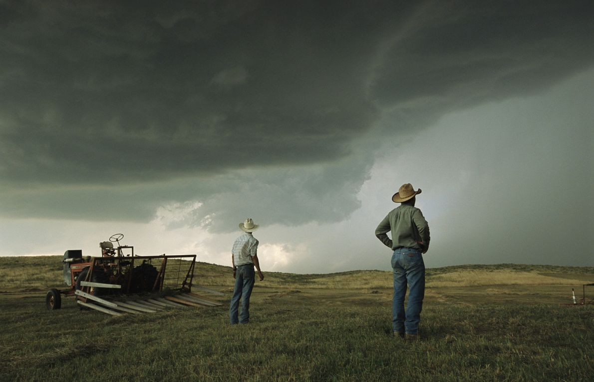 A couple of farmers pause from their work as they survey the looming threat from growing ...