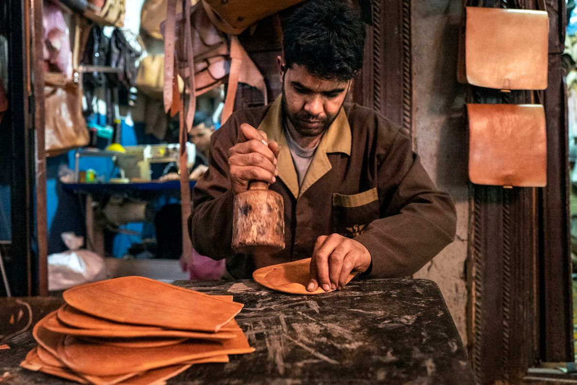 An artisan crafting in his workshop. The traditional wooden tool is used to seal off glued ...