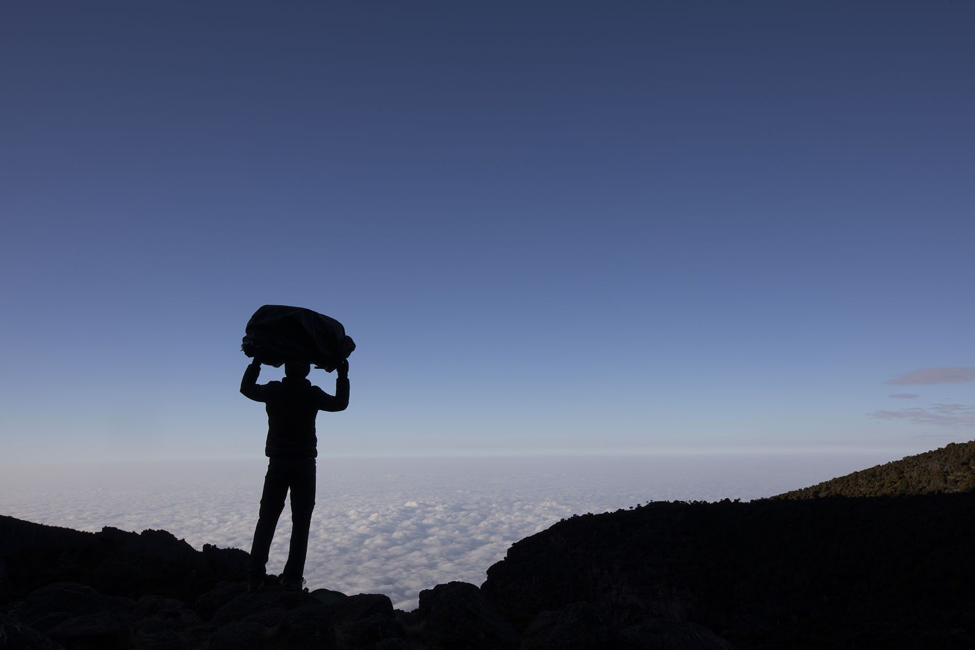Crista Cullen stands atop Mount Kilimanjaro