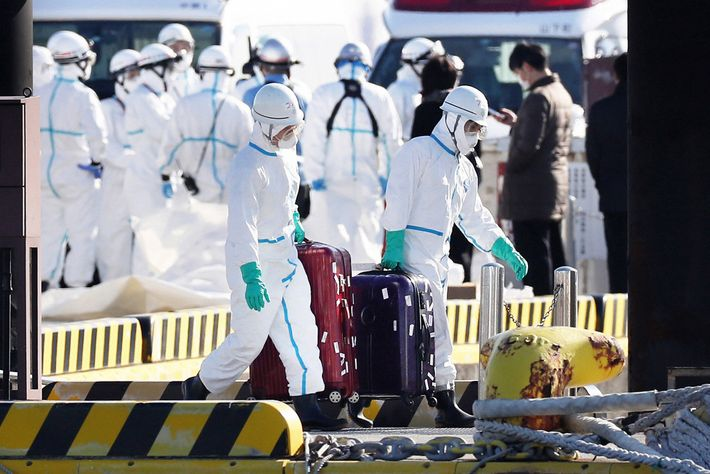 Health officials in protective gear removed suitcases from the Diamond Princess cruise ship in Yokohama, Japan. ...