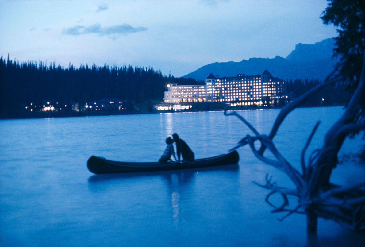 Stealing a romantic moment, a couple kisses on Lake Louise.