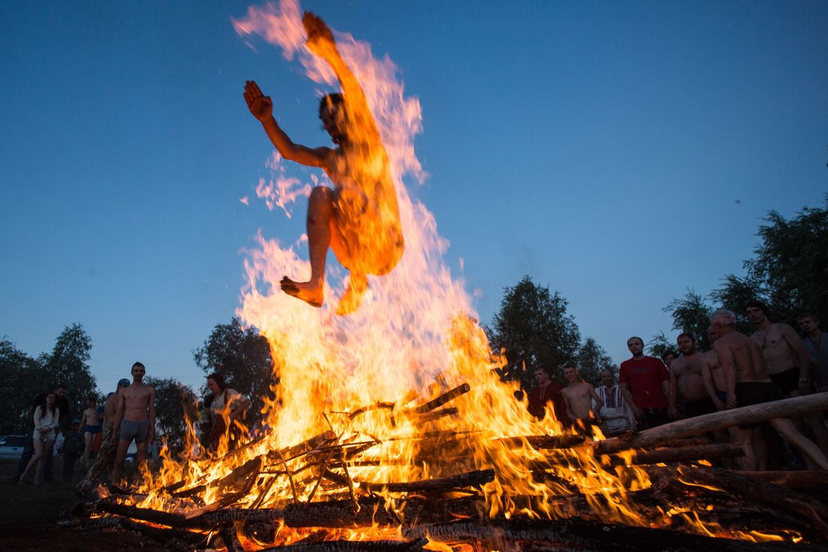 A man jumps over a bonfire during festivities marking Ivan Kupala Day, a pagan summer solstice ...