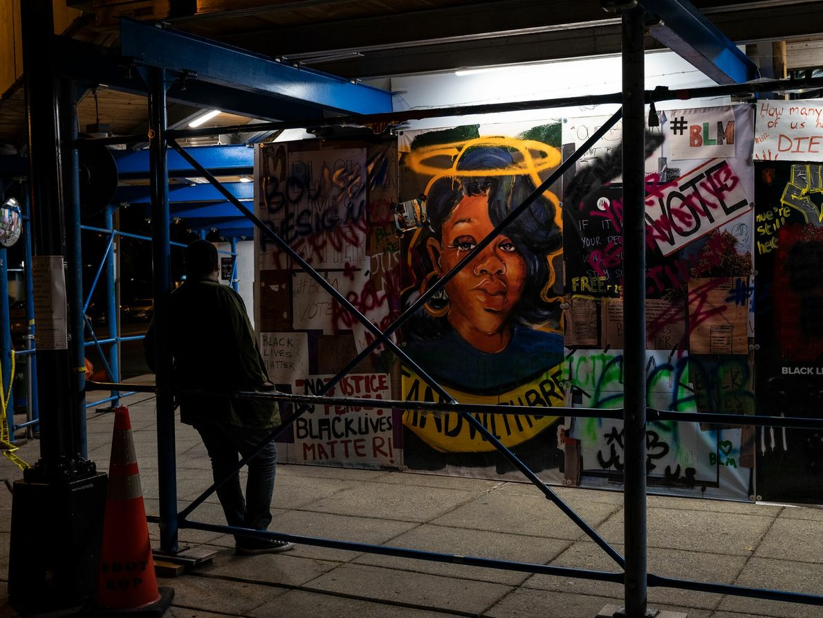 The night before the Commitment March on Washington, a pedestrian stops in front of a mural ...