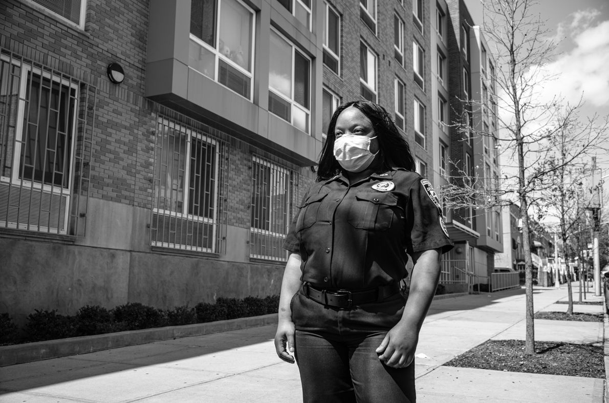 Sekeina Dow, a 911 dispatcher, stands outside her apartment building before heading to work. Since a ...