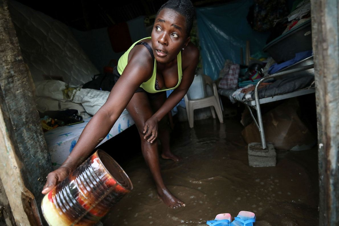 A woman uses a can to remove water from her house after Hurricane Irma struck Fort ...